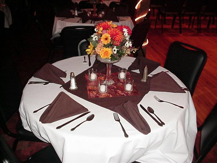 table set with folded napkins, eating utensils, and a flower vase centerpiece
