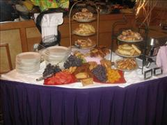 a dessert table with assorted fruits and pastries