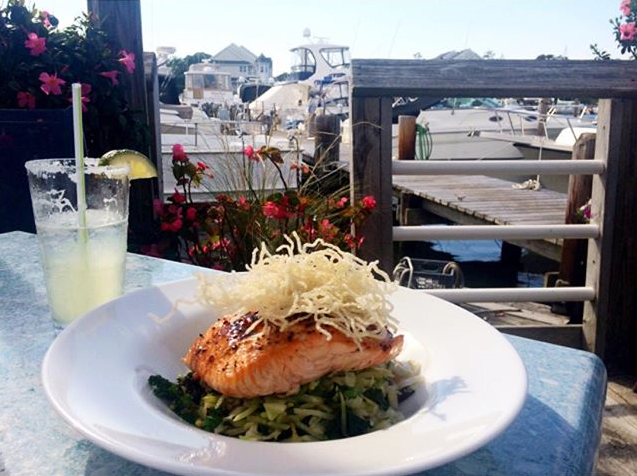 plate with salmon served over greens with a side of lemonade