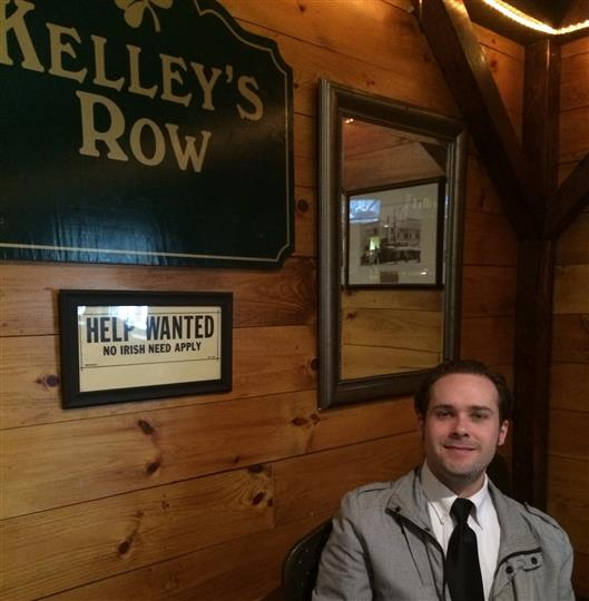 male standing in front of kelley's row sign
