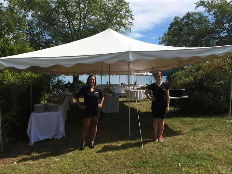 two employees standing under a tent