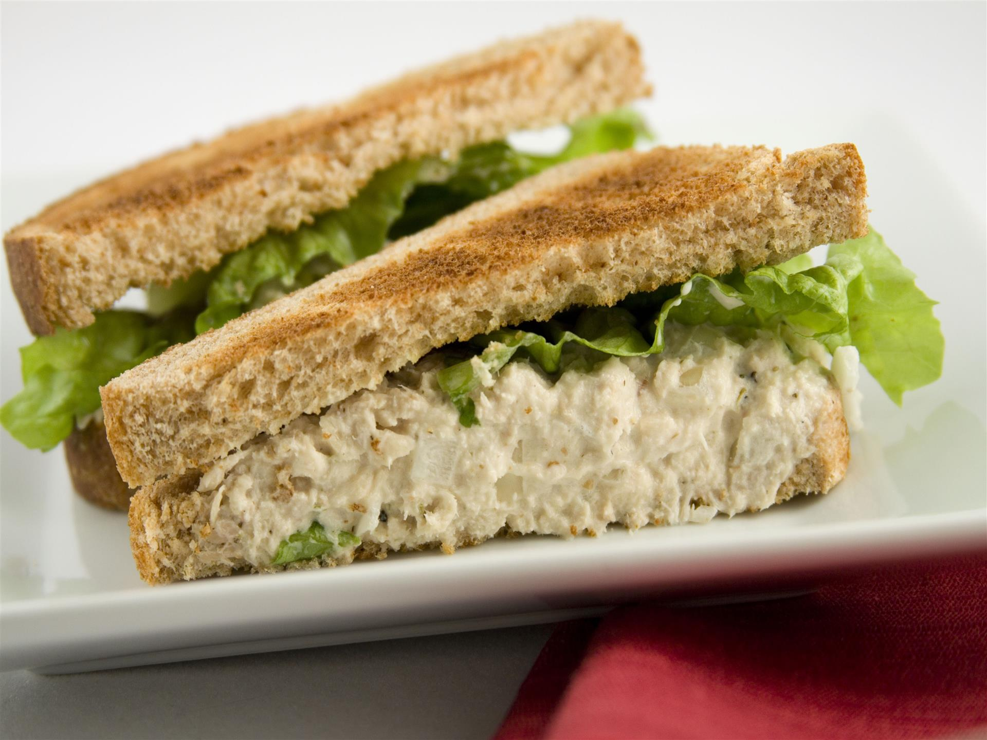 chicken salad sandwich with lettuce cut in half