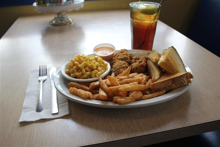 Fish and french fries served with tartar sauce, a side of pasta salad and a glass of coke
