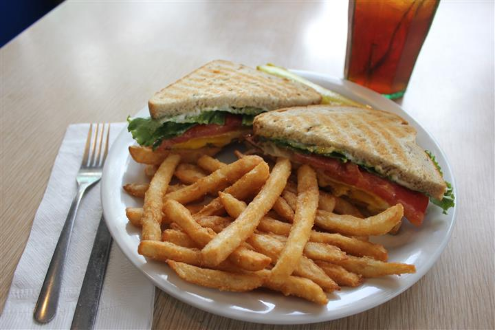 Club sandwich with french fries and a glass of coke