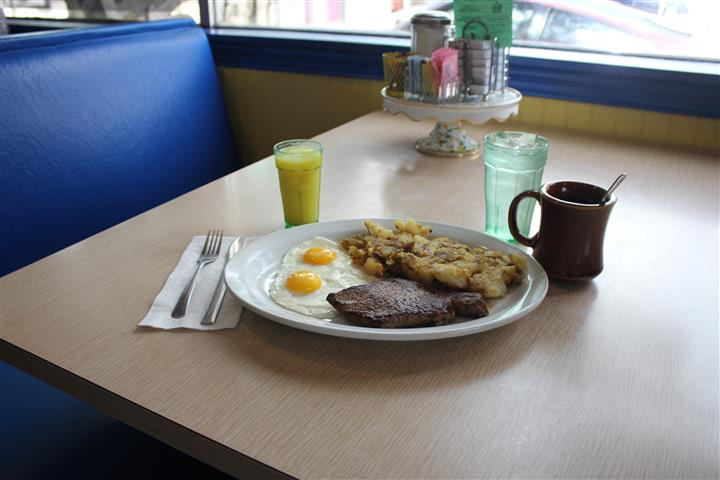 A steak with two fried eggs and home fries, a glass of orange juice, a glass of water, and a coffee