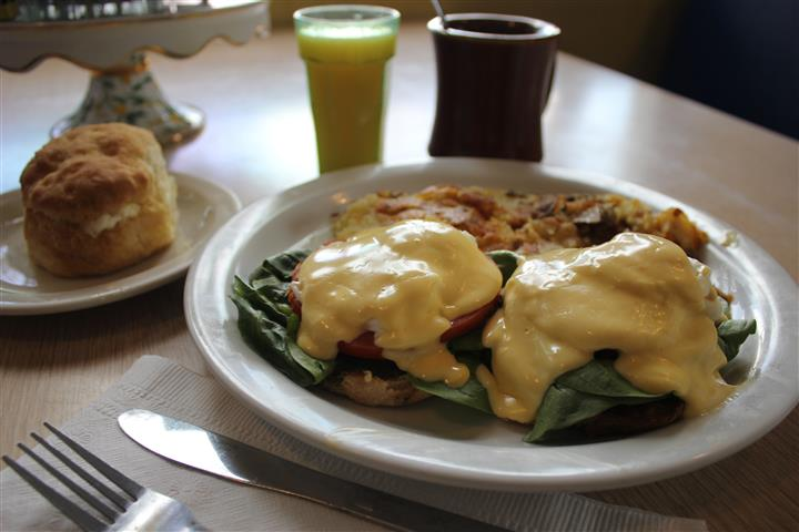 A benedict served with home fries, a glass of orange juice and a coffee