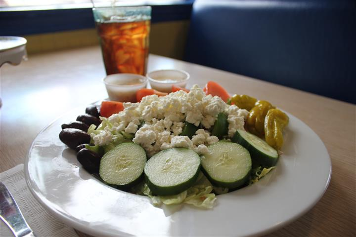 A greek salad with two dressings and a glass of coke
