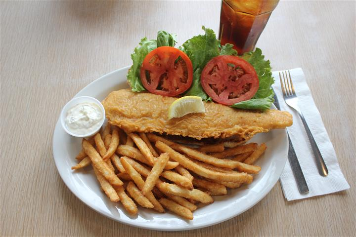 Fish filet and french fries served with a side salad, dipping sauce and a glass of coke