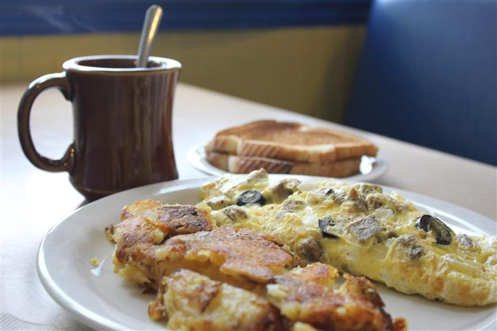 A Greek village omelet served with home fries toast and a cup of coffee
