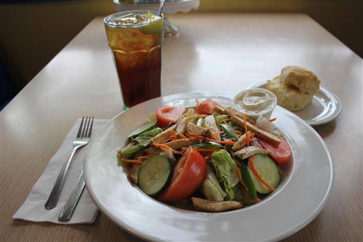 A fresh vegetable salad topped with chicken strips, and served with bread and a glass of coke