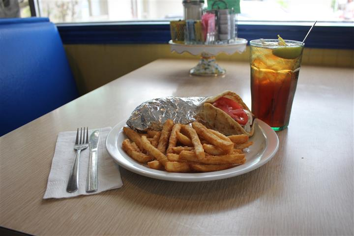 A pita sandwich served with french fries and a glass of coke