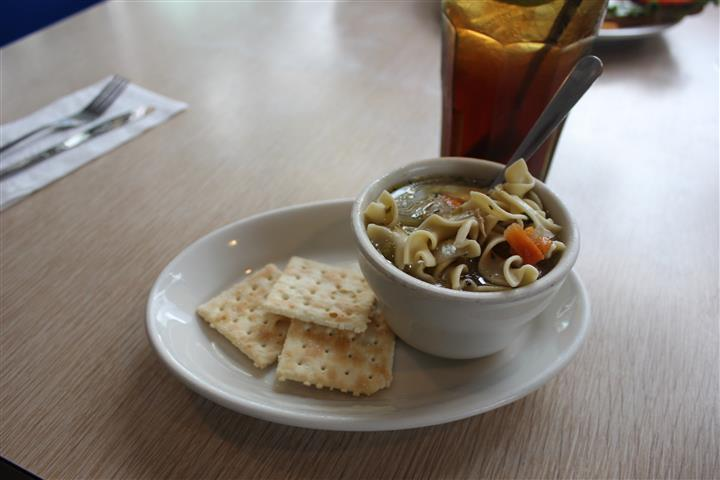 A bowl of soup served with crackers and a glass of coke