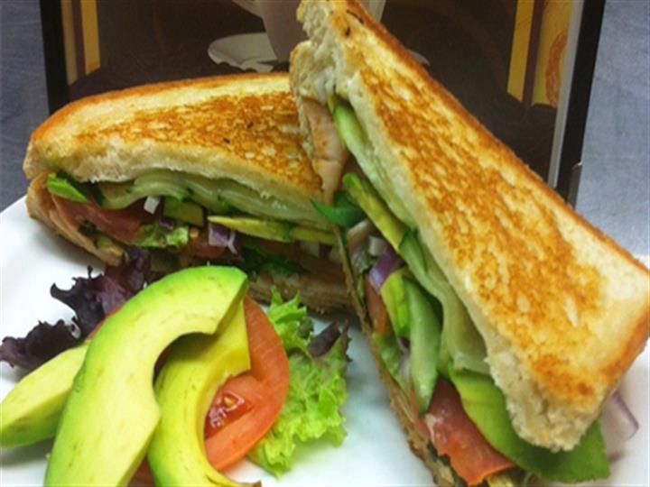 Toasted sandwich with a side of avocado and tomatoes