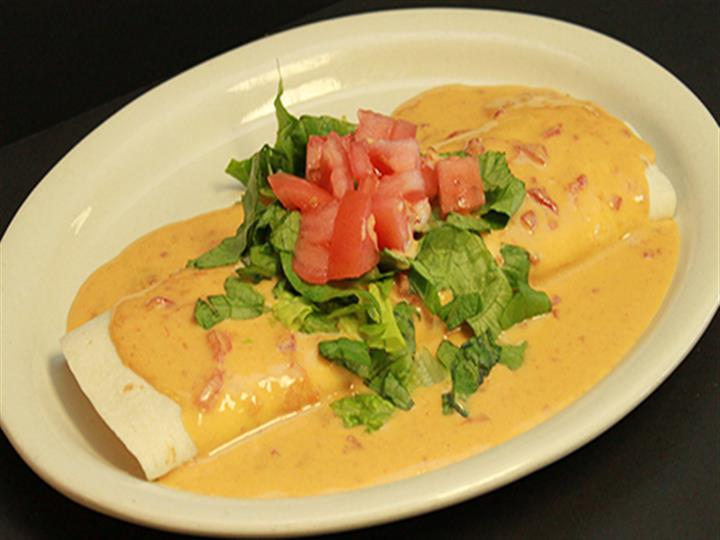 Burrito in gravy topped with lettuce and tomatoes