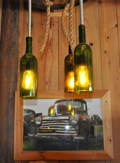 wine bottle chandeliers over photograph on wall of vintage truck