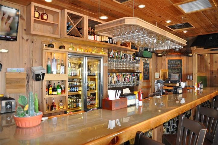 Bar counter in front of shelves and refrigerated section for alcoholic beverages
