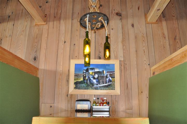 Wine bottle Chandelier over dining area with a painting of a truck