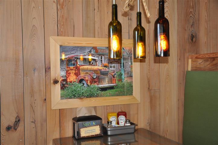 Wine Bottle Chandeliers next to painting of a rusty truck