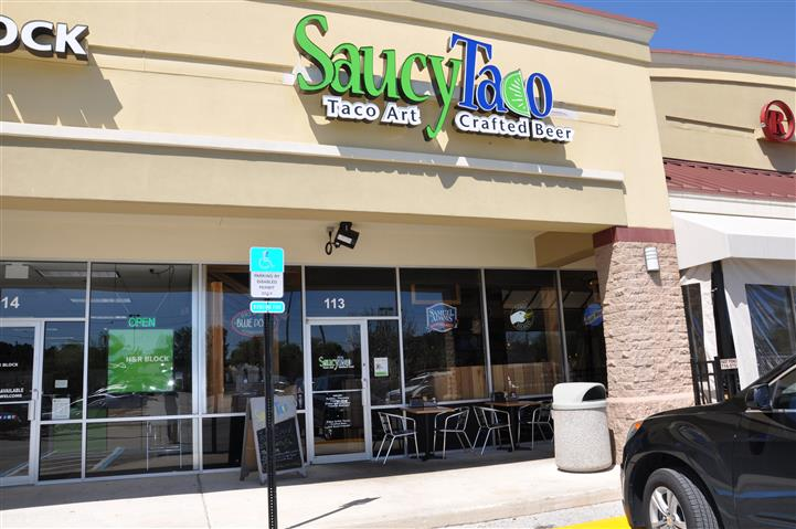 Saucy taco sign and the stores front window