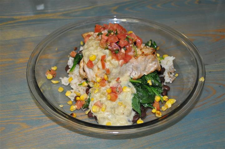 Fish with corn and tomatoes over bed of spinach