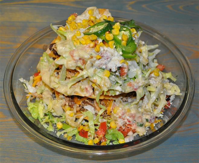 Taco salad with corn, sour cream, tomatoes, jalapenos