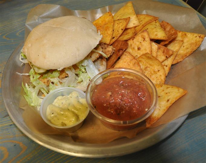 Fish sandwich with side of chips and salsa