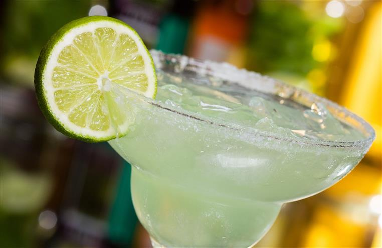 margartia on the rocks in a glass with salted rim and lime wedge garnish