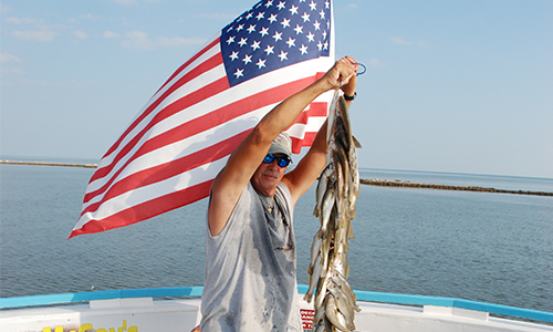 Man holding string of multiple small fish on boat. American flag and open water background