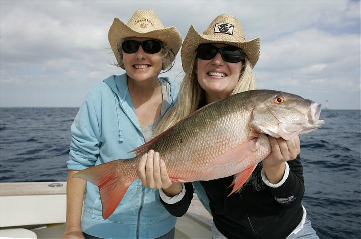Two women smiling on a boat, holding a big fish