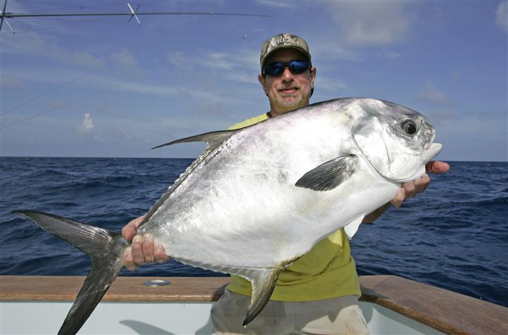A man smiling on a boat, holding a big fish