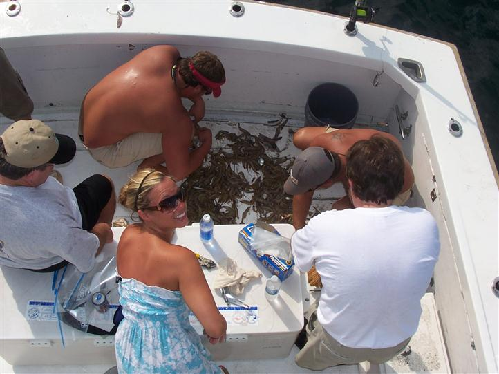 Four men and a woman on a boat, watching fish they just caught