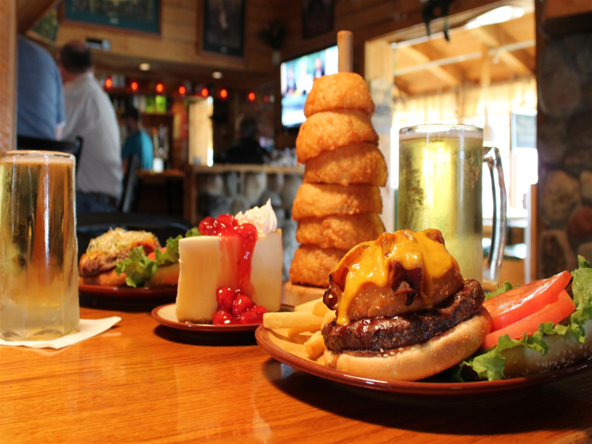 cheeseburger with lettuce, tomato, fries, onion rings, two mugs of beer and cheesecake on a table
