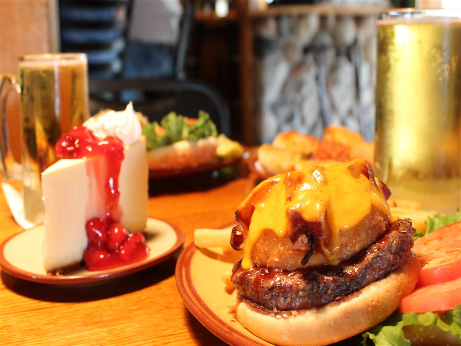 close-up view of cheeseburger with lettuce, tomato, fries, onion rings, two mugs of beer and cheesecake on a table