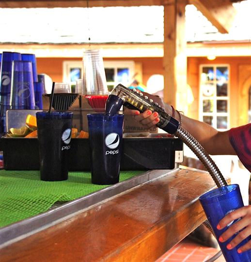 Bartender filling up drinks in a Pepsi cup
