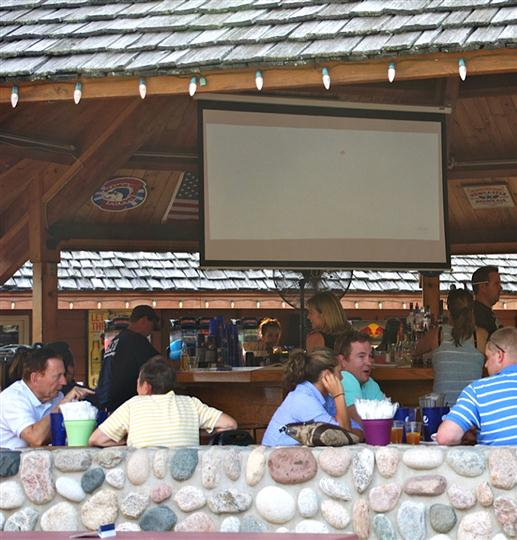 Outdoor Patio with projector screen and people socializing