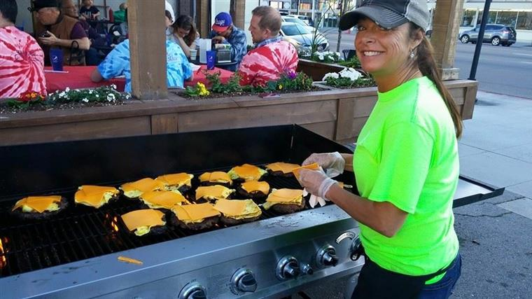 female smiling cooking cheeseburgers on a grill