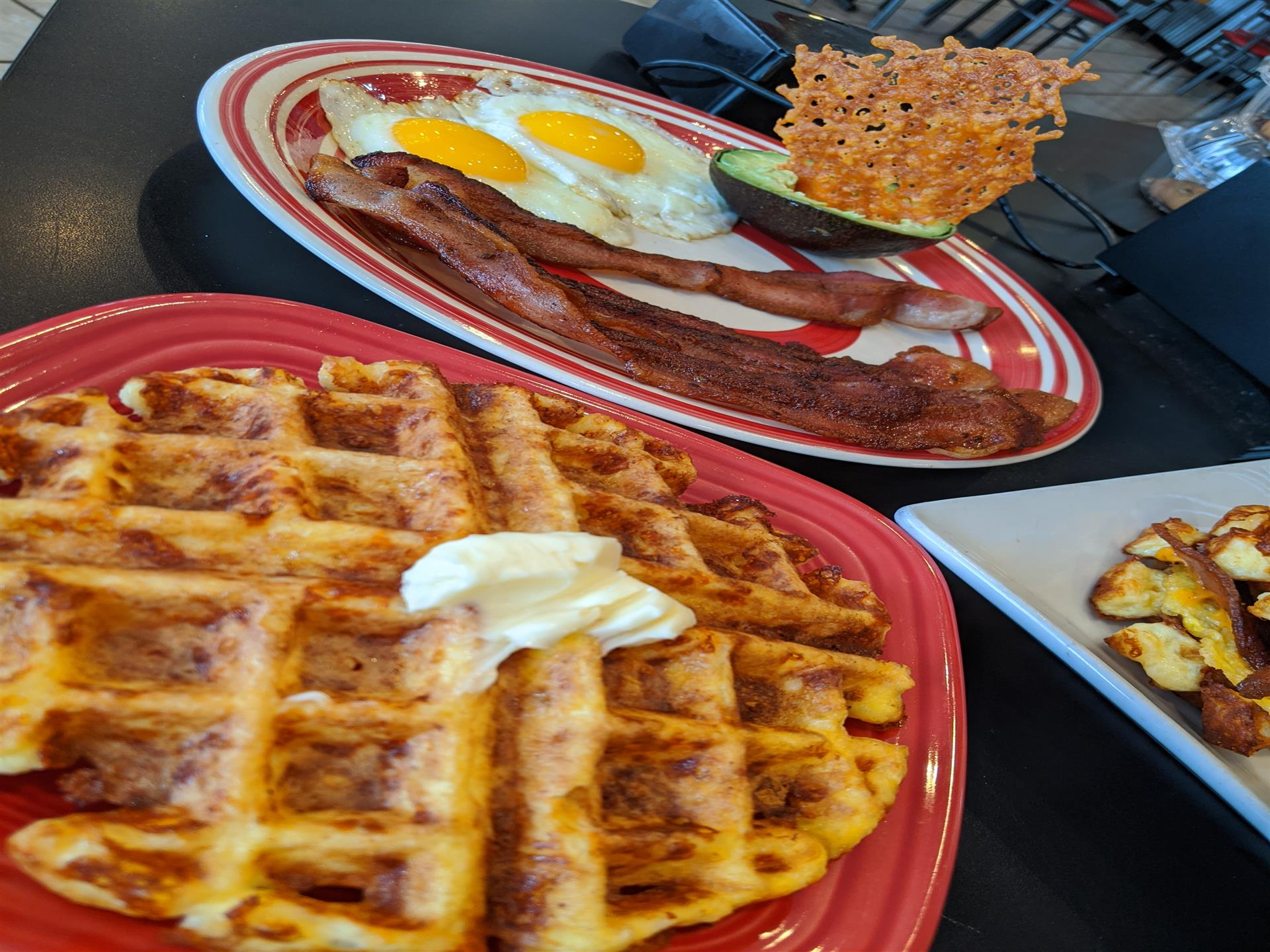A waffle with butter next to bcaon and eggs