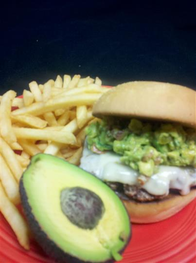 cheeseburger topped with guacamole and a side of french fries