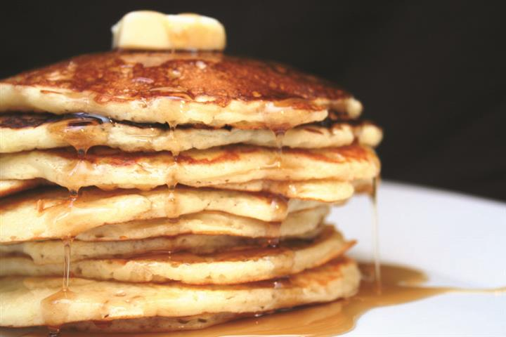 tall stack of pancakes topped with butter and syrup