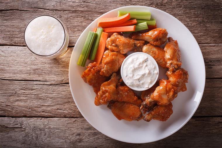 Buffalo wings, carrots, celery, blue cheese on white plate with beer on wooden table.