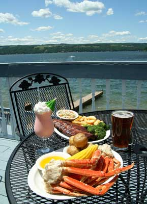 Crab legs with corn on the cob and potatoes in front of a river.