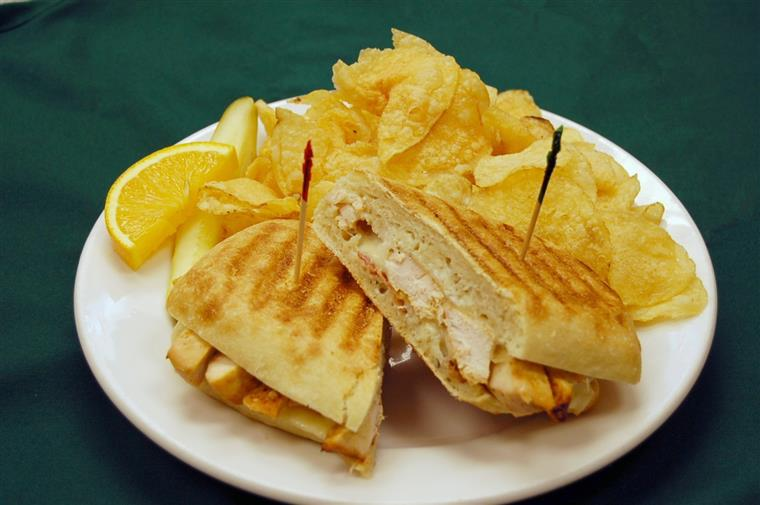 Panini bread sandwiches with potato chips on white plate