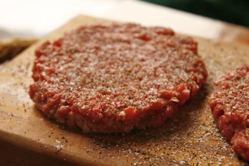 Seasoned raw hamburger on wood cutting board.