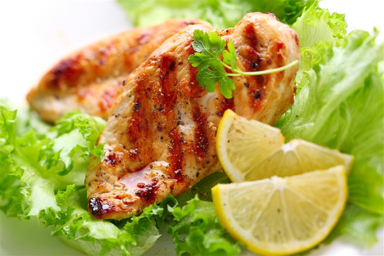 Grilled chicken breast, lemon slices over lettuce.