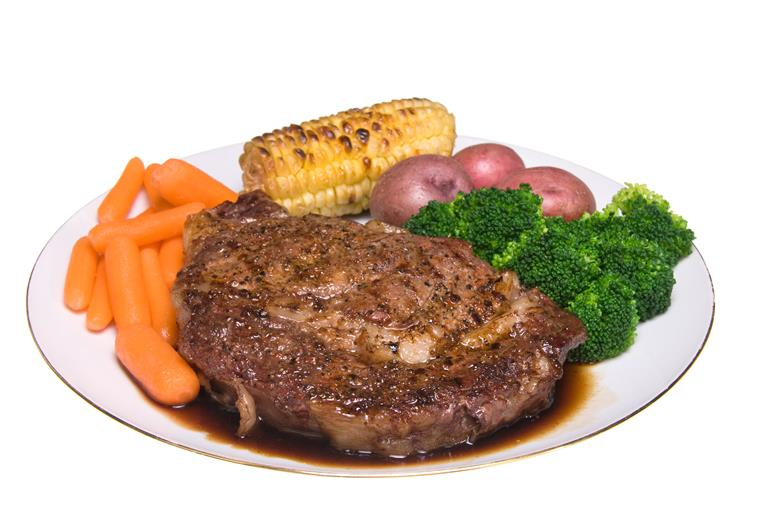 Steak with assorted vegetables on plate.