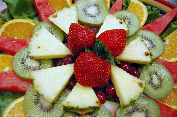 Close up of fruit platter with kiwi, strawberries and pineapple, orange and watermelon.