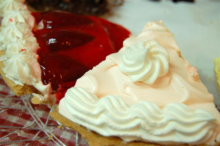 Close up of two different pie slices. One pie is cherry and the other is with a white cream frosting.