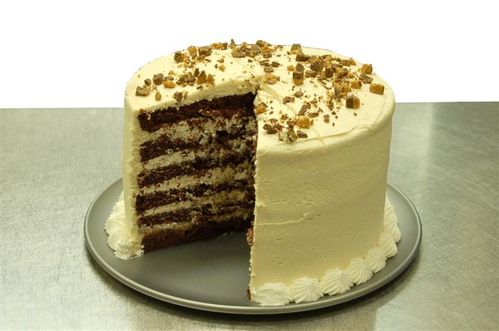 6 layer chocolate cake with a large slice cut out to see the inside. Covered with chocolate candy topping.