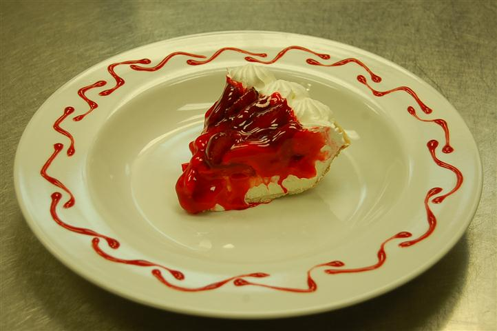 Slice of cake topped with red fruit sauce.