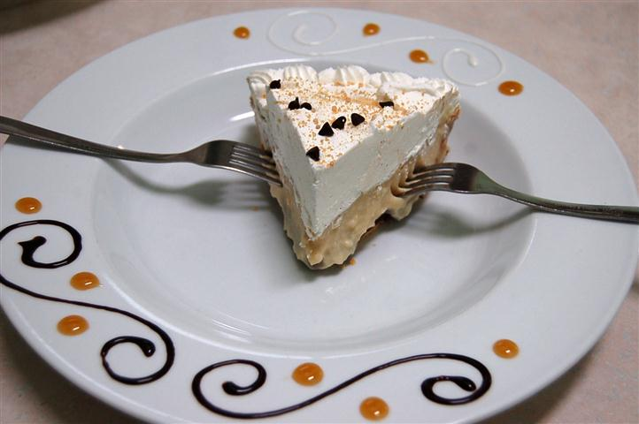 Small slice of pie on a white plate and two forks.